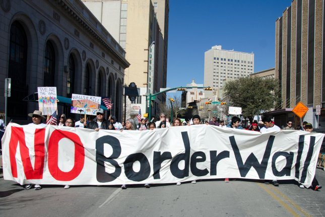 Protesters hold a sign against building a border wall between the U.S. and Mexico during a march in El Paso, Texas, on Saturday. Photo by Natalie Krebs/UPI