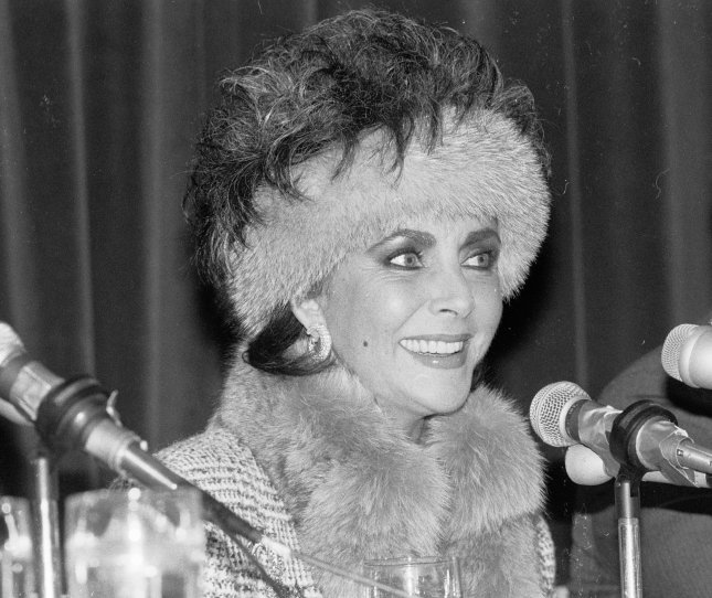 1/14/1987 - New York: A beaming Elizabeth Taylor appears at a press conference here 1/14 at which it was announced that the actress, in collaboration with Parfums International, ltd., the prestige fragrance group of the Prince Matchabelli Div. of Chesebrough-Pond's Inc., would introduce a new fragrance as part of a major business agreement. (UPI Photo/Ezio Peterson/Files)