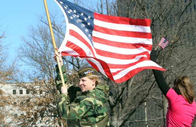 A women veteran holds an American flag while riding on a truck in a parade in St. Louis on January 28, 2012. Thousands of people lined a parade route in downtown St. Louis for the nation's first parade to honor those who have served in Iraq and Afghanistan. UPI/Bill Greenblatt