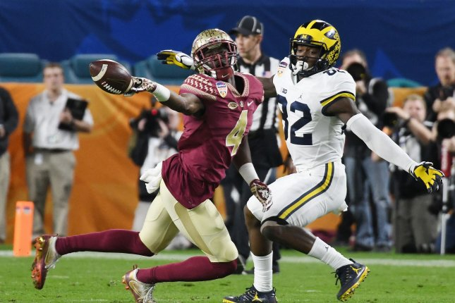 Florida State Seminoles RB Dalvin Cook is defended by Michigan Wolverines's Amara DDarboh in the second quarter of the 2016 Capital One Orange Bowl at Hard Rock Stadium in Miami Gardens, Florida on December 30, 2016. File photo by Gary Rothstein/UPI