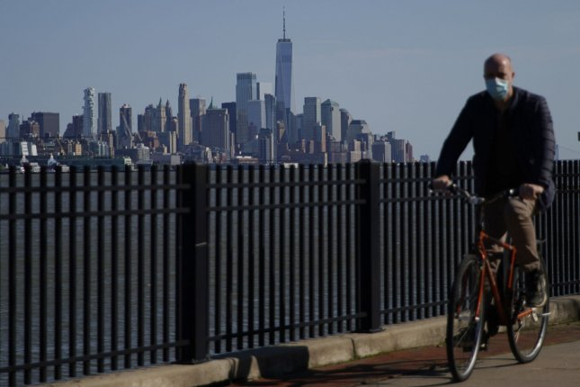 A bicyclist rides in Hoboken, N.J., on Sunday with a view of the Manhattan skyline in the background. Photo by John Angelillo/UPI