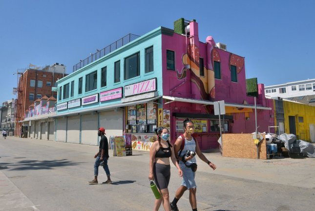 Beachgoers, with and without masks walk past closed businesses on the Venice Beach boardwalk in Los Angeles in May as recreational centers started to reopen. Researchers say early lockdowns helped to stem spread of the new coronavirus. Photo by Jim Ruymen/UPI