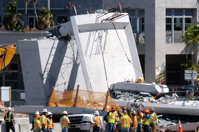Rescue workers search the site of a pedestrian bridge that collapsed only days after it was installed over southwest 8th Street in Miami, Florida, on March 16. File Photo by Gary Rothstein/UPI