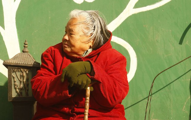 An elderly Chinese woman sits in the midday sun in downtown Beijing March 11, 2011. UPI/Stephen Shaver