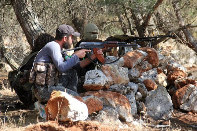 Fighters from a coalition of rebel groups called Jaish al-Fatah, or Army of Conquest, take positions during fighting with the Syrian regime near the town of Psoncol in the Idlib countryside, Syria, on June 5, 2015. Photo by Omar Haj Kadour/ UPI