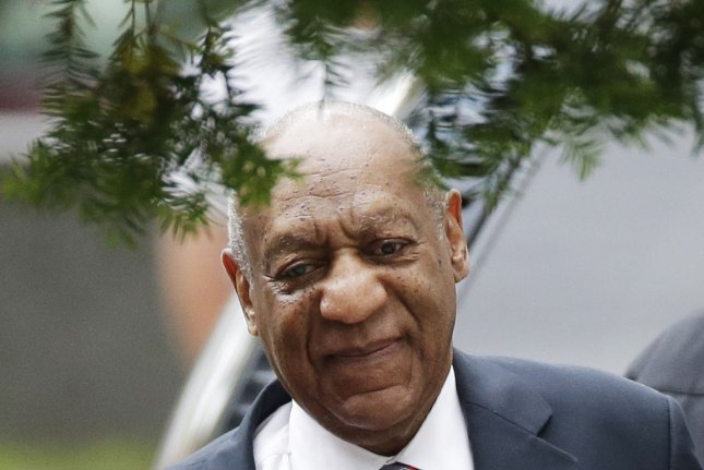 Bill Cosby is escorted into Montgomery County Courthouse for the third day of his sexual assault trial in Norristown, Pa., on Wednesday. On Wednesday, the mother of Cosby's accuser, Andrea Constand, said the entertainer attempted to convince her that what her daughter said was sexual assault was in fact consensual. Photo by John Angelillo/UPI