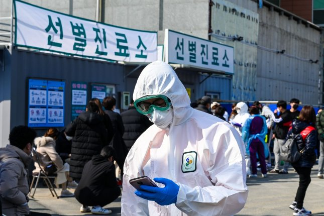 A hospital worker in a biohazard suit checks his phone at Daegu Medical Center in South Korea on February 21. Photo by Thomas Maresca/UPI