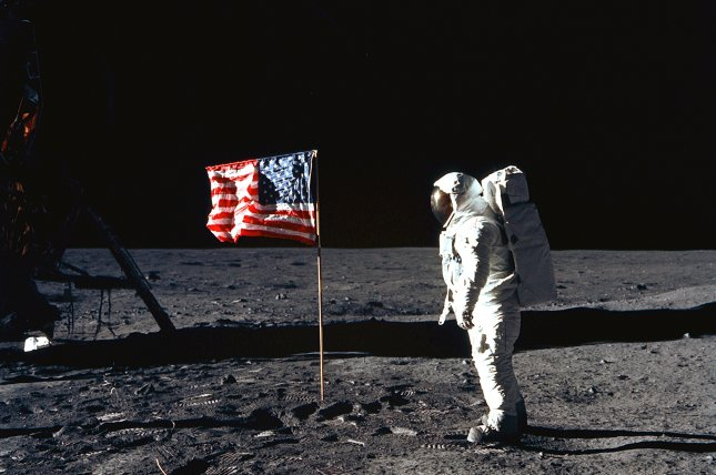 Astronaut Edwin E. Aldrin, Jr., lunar module pilot, poses for a photograph beside the deployed United States flag during Apollo 11 Extravehicular Activity (EVA) on the lunar surface. The Lunar Module (LM) is on the left, and the footprints of the astronauts are clearly visible in the soil of the Moon. Astronaut Neil A. Armstrong, commander, took this picture with a 70mm Hasselblad lunar surface camera. File photo by NASA/UPI