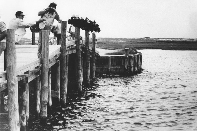 Mourners throw flowers off the Dike Bridge on July 19, 1979, the 10th anniversary of the day Sen. Edward Kennedy's car plunged off the bridge, killing Mary Jo Kopechne. UPI File Photo