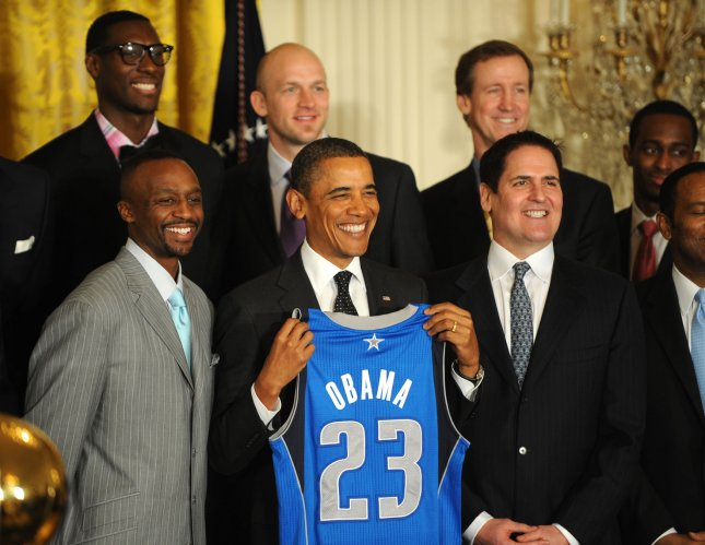 U.S. President Barack Obama holds a Dallas Mavericks jersey as he poses with owner Mark Cuban (R) and the rest of the team during a ceremony honoring the 2011 NBA Champions in the East Room of the White House on January 9, 2012 in Washington, DC. Obama shared some laughs as he congratulated Dallas for their first National Basketball League Championship. UPI/Pat Benic