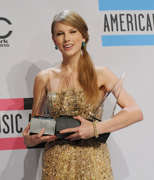 Taylor Swift appears backstage with the three awards she garnered at the 39th American Music Awards at Nokia Theatre in Los Angeles on November 20, 2011. UPI/Jim Ruymen