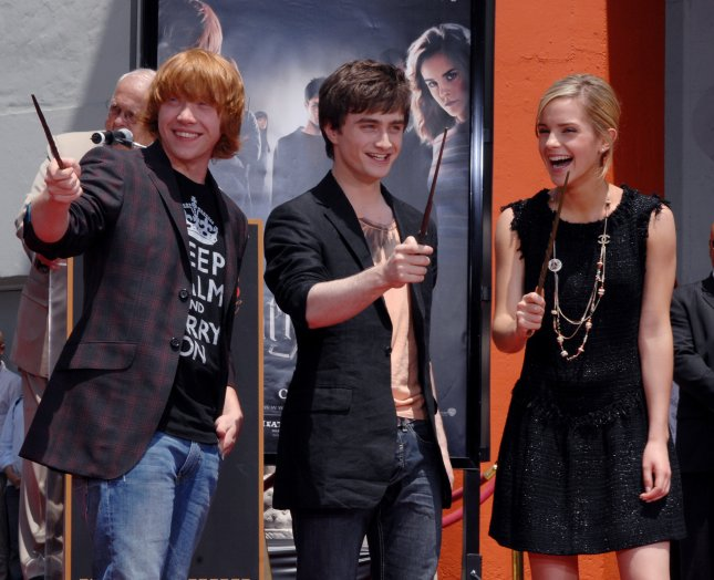 The three young stars of the Harry Potter films Rupert Grint, Daniel Radcliffe and Emma Watson (L-R) hold their magic wands during a hand and foot print ceremony in the forecourt of Grauman's Chinese Theatre in the Hollywood section of Los Angeles on July 9, 2007. Harry Potter and the Order of the Phoenix, the fifth film in the series, will be released worldwide this week. (UPI Photo/Jim Ruymen)..