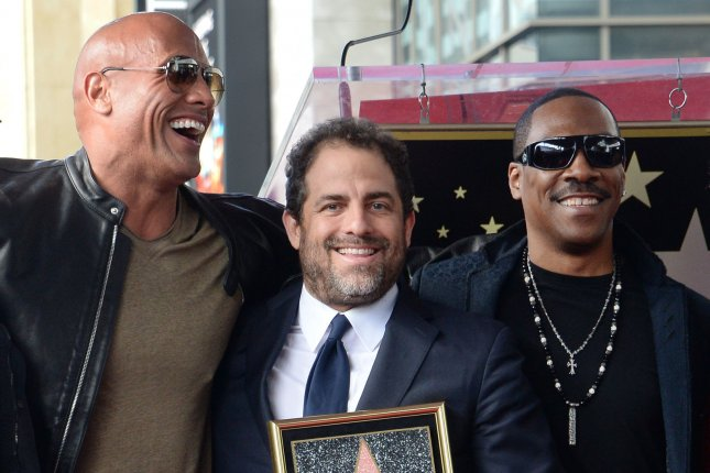 Director Brett Ratner (C), pictured with by Dwayne The Rock Johnson (L) and Eddie Murphy (R), has been accused of sexual harassment by six actresses including Olivia Munn and Natasha Henstridge. File Photo by Jim Ruymen/UPI