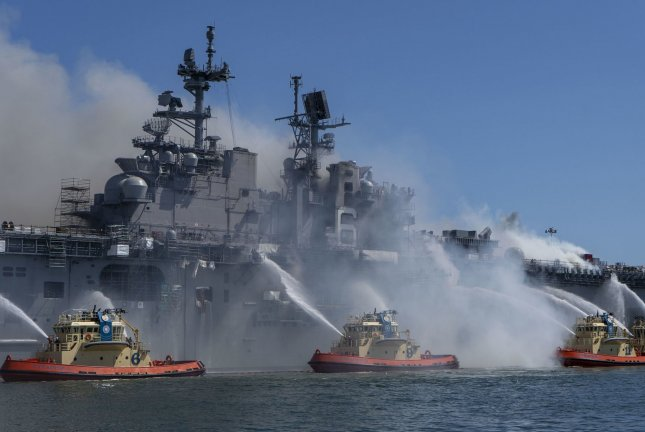 Sailors and federal firefighters combat a fire onboard USS Bonhomme Richard (LHD 6) at Naval Base San Diego July 12. Multiple sources have reported that federal agents are questioning a sailor in connection with the blaze, which burned for four days and injured 63 people. Photo by Christina Ross/U.S. Navy