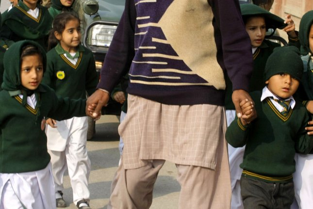 Students are escorted from the Army Public School in Peshawar, Pakistan, after an attack by Taliban gunmen on Dec. 16, 2014. Many of the children who survived are traumatized. File Photo by Sajjad Ali Queshi/UPI