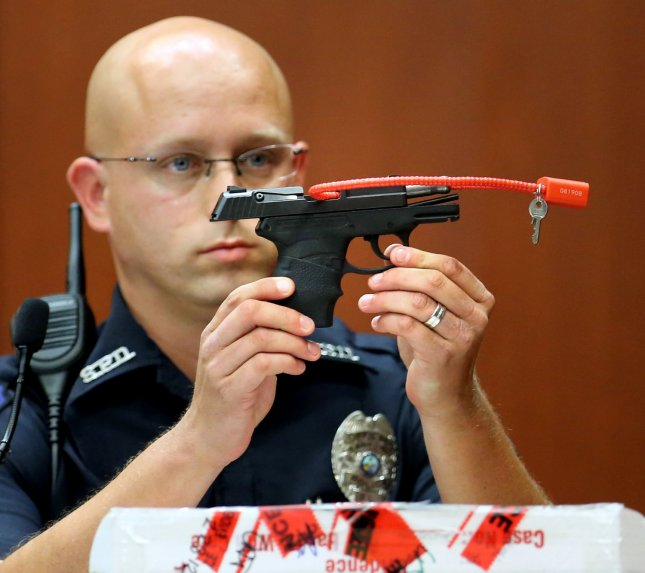 Sanford Police officer Timothy Smith holds up the gun that was used to kill Trayvon Martin, while testifying on day 15 of George Zimmerman's trial in Sanford, Floa., in 2013. Zimmerman was acquitted of second-degree murder. Now Zimmerman is trying to auction off the gun. File Photo by Joe Burbank/Pool