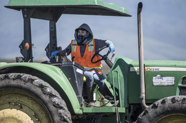 A masked farm worker is seen driving a tractor in Salinas, Calif., on April 28. Nearly 70% of Americans have a positive view of the farming and agriculture industry, a Gallup survey showed Tuesday. File Photo by Terry Schmitt/UPI