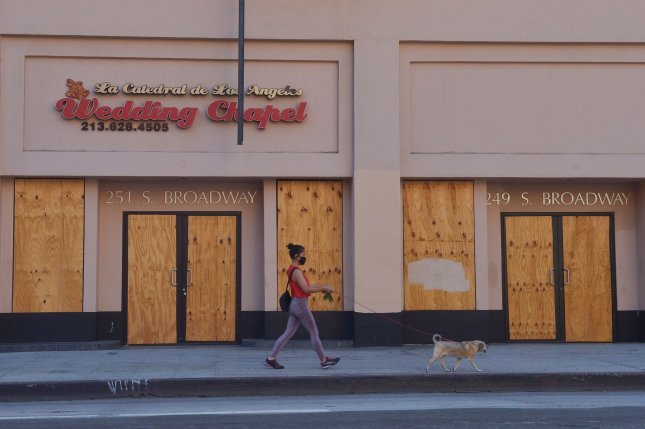 A woman walks her dog past a boarded up wedding chapel in downtown Los Angeles on August 10. The Fed on Friday loosened restrictions on COVID-19 relief loans for small businesses. Filephoto by Jim Ruymen/UPI