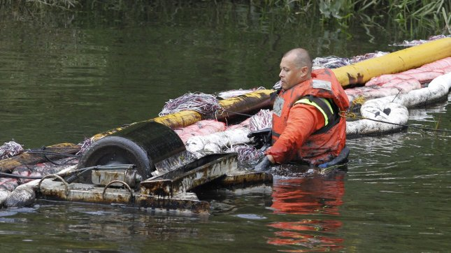 A worker tends to an oil boom on the Kalamazoo River near Battle Creek, Michigan on July 30, 2010. A 30-inch-diameter pipeline ruptured sending between 800,000 and 1 million gallons of oil into nearby Talmadge Creek and the Kalamazoo River. UPI/Brian Kersey