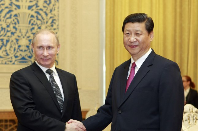 Russian President Vladimir Putin, left, shakes hands with Xi Jinping in Beijing in 2012. File Photo courtesy of Xinhua