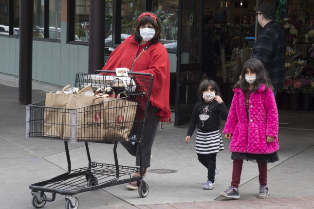 A family leaves a grocery store with supplies in San Francisco on Monday, March 16, 2020. Photo by Terry Schmitt/UPI