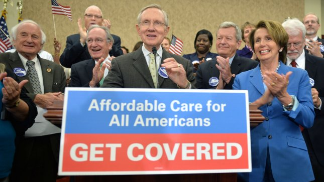 Senate Majority Leader Harry Reid (D-NV) (center) and House Minority Leader Nancy Pelosi (D-CA) (right) applaud with other Democrats at a press conference celebrating the start of open enrollment for the Affordable Care Act, in Washington, D.C. on October 1, 2013. UPI/Kevin Dietsch
