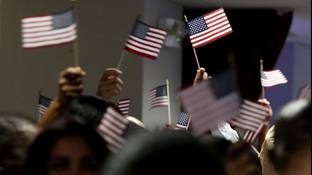 New Citizens of the United States wave American Flags when U.S. Citizenship and Immigration Services officials hold a naturalization ceremony for 150 immigrants in New York City on July 2, 2013. UPI/John Angelillo