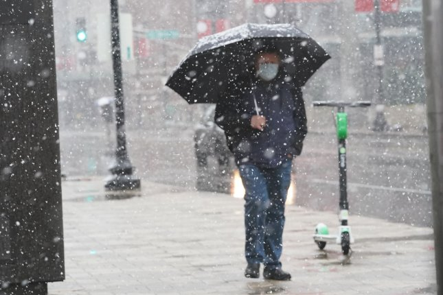 A pedestrian uses an umbrella to shield himself from a heavy snow fall in downtown St. Louis on April 20, 2021. Temperatures dropped from 72 degrees one day earlier to 31 degrees, dropping about one inch of snow on the St. Louis area. File Photo by Bill Greenblatt/UPI
