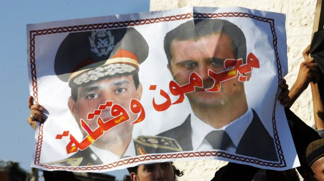 A Palestinian Salafist hold a poster depicting Syria's President Bashar al-Assad (R) and Egypt's army chief General Abdel Fattah al-Sisi with the Arabic words that read criminals and murderers, during a rally in protest of what they say are recent massacres committed against Syrian and Egyptian people, in Rafah in the southern Gaza , August 22, 2013. UPI/Ismael Mohamad
