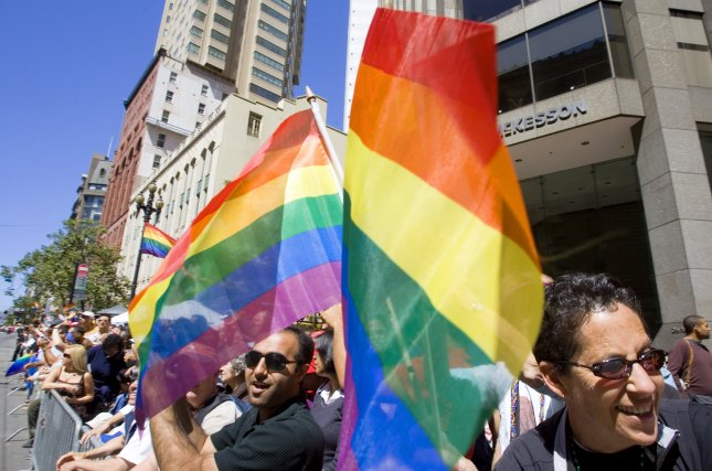 T.J. Turner and his partner Ray wave pride flags along the side of the parade route on Market Street during the 37th annual San Francisco LGBT Pride Parade in San Francisco on June 24, 2007. (UPI File Photo/Aaron Kehoe).