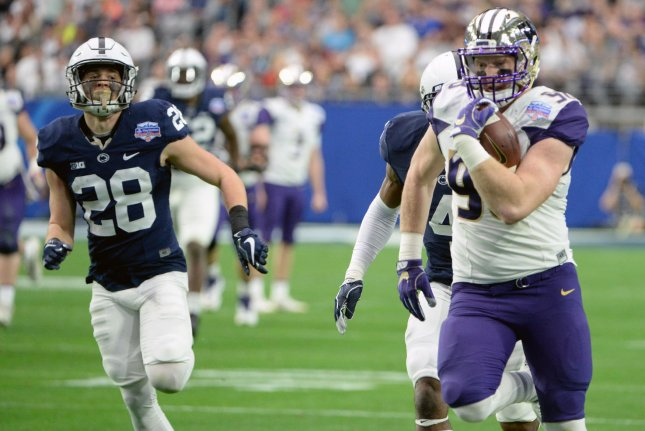Washington Huskies tight end Will Dissly (R) picks up a first down in the first quarter of the PlayStation Fiesta Bowl on December 30, 2017 at University of Phoenix Stadium in Glendale, Arizona. Photo by Art Foxall/UPI