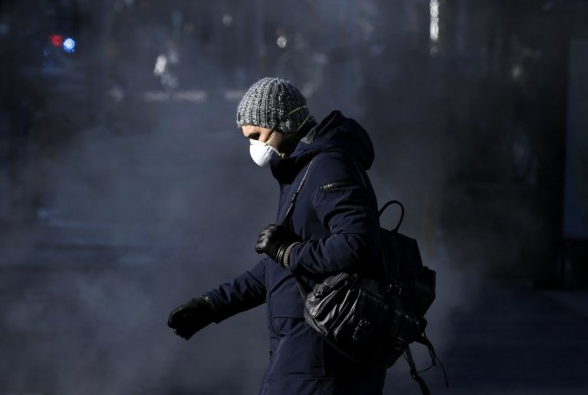 A pedestrian wears gloves and a protective mask near Lincoln Center in New York City on March 24. Photo by John Angelillo/UPI