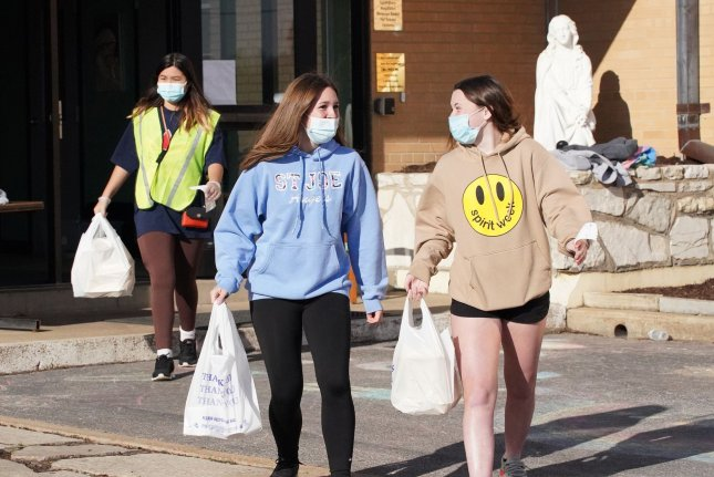 Volunteers take dinner orders to customers in their cars amid the COVID-19 pandemic on Good Friday, at St. Mary Magdalen School in Brentwood, Missouri. Photo by Bill Greenblatt/UPI