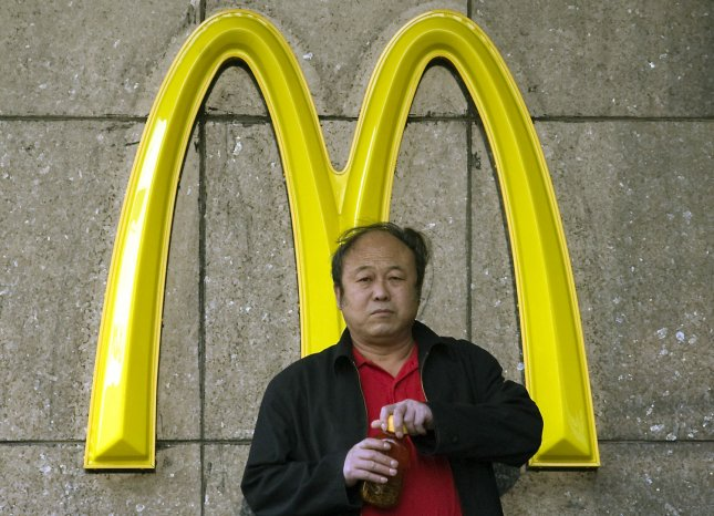 A Chinese man escapes the midday sun to drink his tea in front of a McDonalds in central Beijing November 19, 2008. McDonalds Corp, the worlds largest restaurant company, plans to add 175 restaurants in China in 2009 after opening its 1,000th outlet in the country. (UPI Photo/Stephen Shaver)