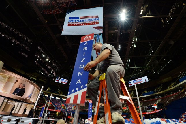 Workers position state delegation signs at the Quicken Loans Arena in Cleveland on Friday. The convention starts on Monday. Photo by Pat Benic/UPI