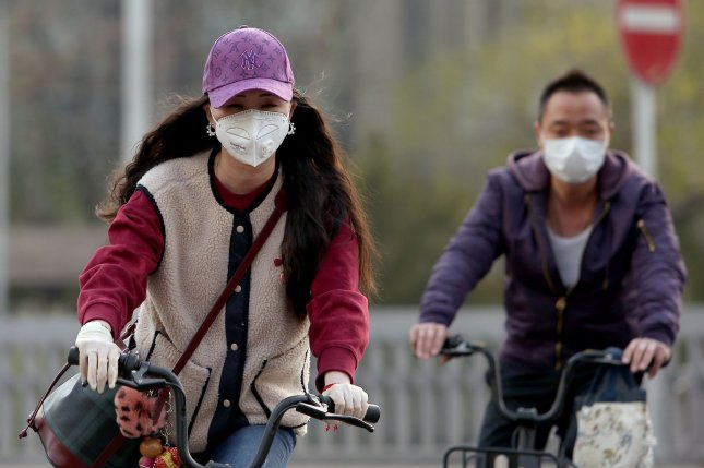 People continue to wear protective face masks outside even though coronavirus restrictions have begun to ease as the number of new cases and new deaths has declined. Photo by Stephen Shaver/UPI