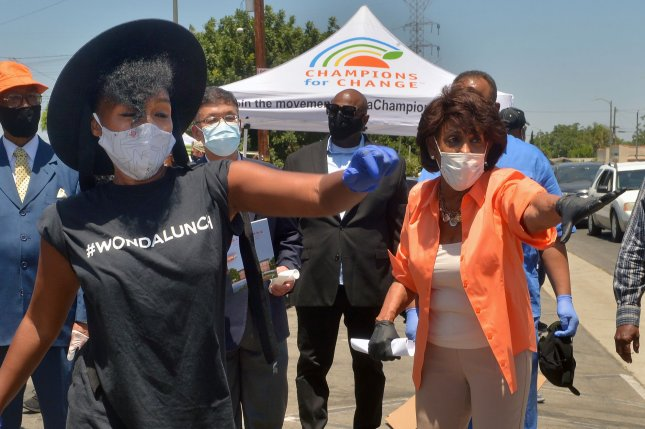 Janelle Monáe (L) and Democratic Congresswoman Maxine Waters help distribute fresh food to families impacted by the coronavirus pandemic Tuesday in Los Angeles. Photo by Jim Ruymen/UPI