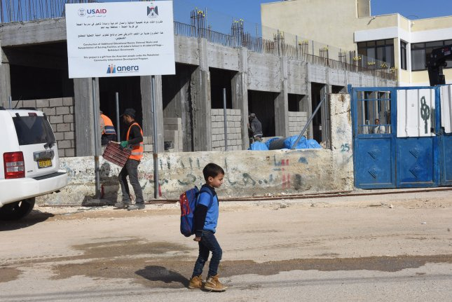 A Palestinian boy walks past construction workers building an extension to a girl's school in Al-Jabba, near Bethlehem, West Bank, on Wednesday. The $1.4 million dollar project will be terminated due to the elimination of U.S. aid. Photo by Debbie Hill/UPI