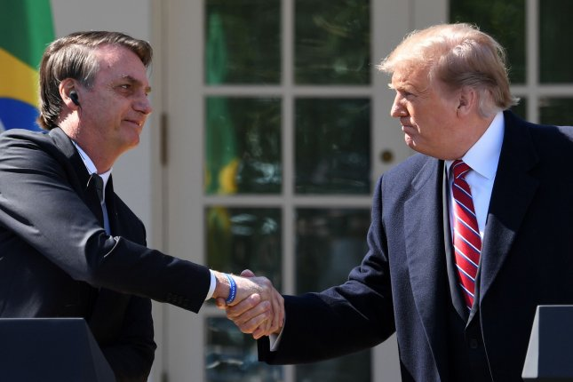 President Donald Trump shakes hands with Brazilian President Jair Bolsonaro at a joint press conference in Washington, D.C., in March 2019. File Photo by Pat Benic/UPI