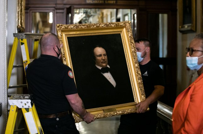 Staff with the Architect of the Capitol remove a portrait of former Confederate House Speaker James Lawrence Orr outside of the House chambers Thursday in Washington, D.C.. Pool Photo by Nicholas Kamm/UPI