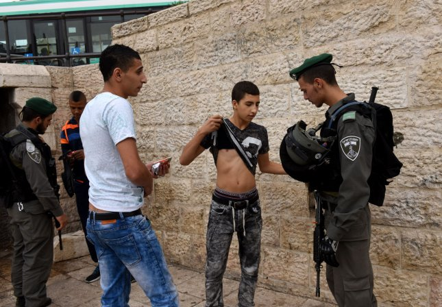 An Israeli border police makes a Palestinian raise his shirt during a security check ahead of Muslim Friday prayers outside the Damascus Gate in the East Jerusalem, Oct. 23. For the first time in several weeks of violence, Israel did not limit the age of Muslims who could enter the al-Aqsa Mosque Compound to pray in an attempt to ease tensions with the Palestinians. A movement whose leader has been accused of being an agitator for the safety of the mosque was outlawed by the Israeli government. Photo by Debbie Hill/UPI