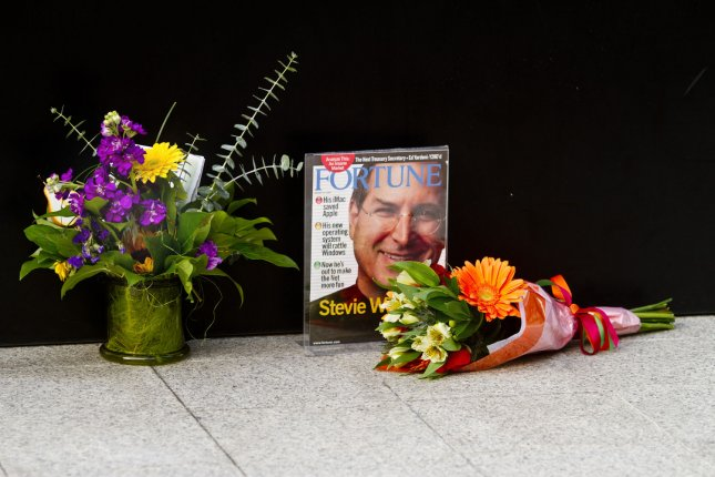 People place flowers and a Fortune Magazine cover in front of Apple headquarters in Cupertino, California on October 5, 2011, after it was announced that Steve Jobs had died at the age of 56. Jobs was the founder and former CEO of Apple that transformed personal computer technology and invented devices such as the iPod, iPhone and iPad. UPI/Mohammad Kheirkhah