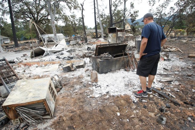 Cal Fire Capt. Justin Galvan on Tuesday views his home, destroyed by the Valley Fire in Middletown, Calif. Galvan's father and sister also lost their homes to the blaze. Wildfires have sprung up again all over drought parched California. Photo by Mathew Sumner/UPI