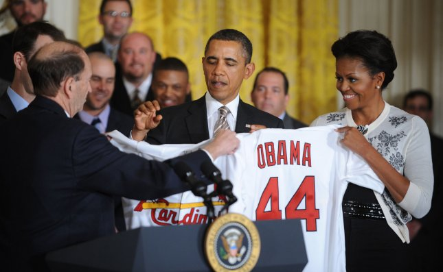 First Lady Michelle Obama and U.S. President Barack Obama receive St. Louis Cardinals jerseys from Cardinals Chairman William DeWitt, Jr and his son Cardinals President William DeWitt III during a ceremony honoring the World Series Champions St. Louis Cardinals in the East Room at the White House on January 17, 2012 in Washington, DC. It was also the First Lady's birthday, she turned 48. UPI/Pat Benic