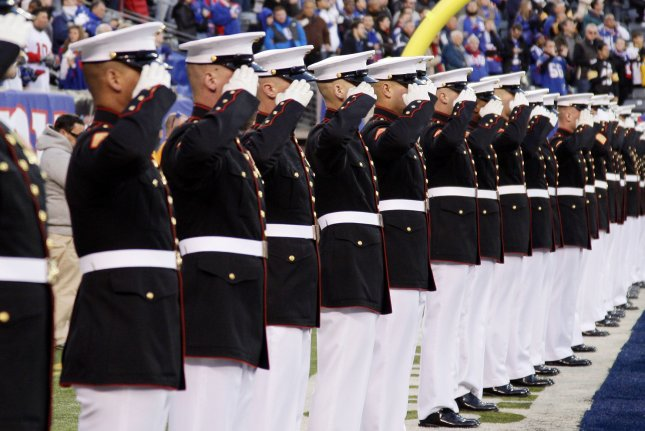 U.S. Marines salute the field for the national anthem before the New York Giants play the Pittsburgh Steelers on November 4, 2012, at MetLife Stadium in East Rutherford, N.J. The U.S. Department of Defense is investigating allegations hundreds of former and current Marines posted nude photos of their female colleagues to a Facebook group. File Photo by John Angelillo/UPI