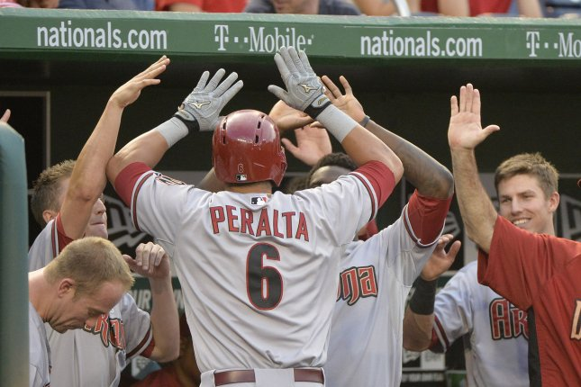 Arizona Diamondbacks' David Peralta is congratulated by teammates after returning to the dugout. File photo by Kevin Dietsch/UPI