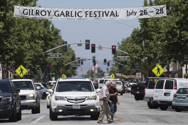 Pedestrians cross Monterey Street in Gilroy, Calif., Monday, under a banner for the city's garlic festival this year, which was attacked by a gunman. Photo by Terry Schmitt/UPI