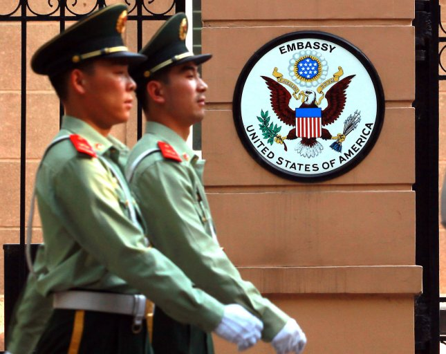 Chinese soldiers march past part of the United States Embassy in Beijing on May 20, 2014. China summoned the U.S. ambassador and the Defense Ministry warned of serious damage to military relations after the United States charged five Chinese army officers with hacking into American companies to steal trade secrets. UPI/Stephen Shaver