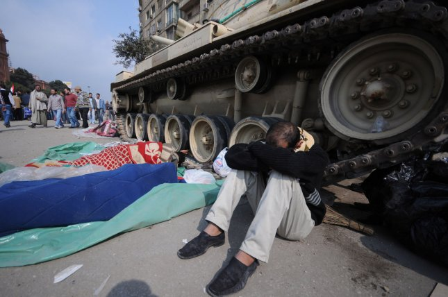 Egyptian anti-government demonstrators camp next to an army tank in Cairo's Tahrir Square on February 7, 2011 on the 14th day of protests calling for the ouster of President Hosni Mubarak. UPI