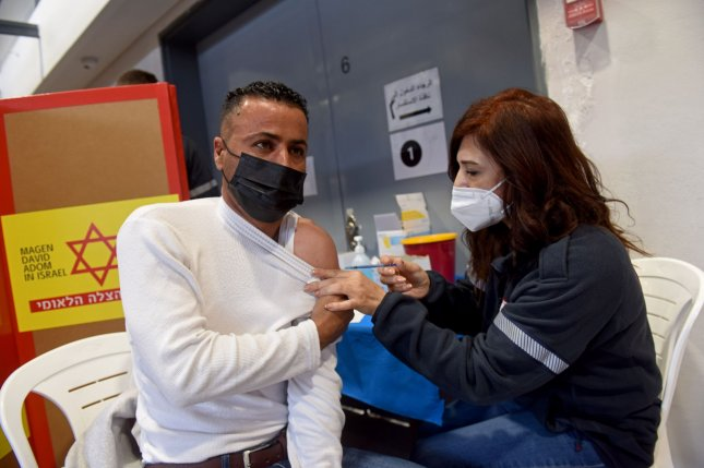 A medic from Israel's Magen David Adam emergency agency inoculates a Palestinian worker with the first dose of the Moderna COVID-19 vaccine at the Lamed Hei Checkpoint between Gush Etzion and Beit Shemesh, on Monday, March 8, 2021. File Photo by Debbie Hill/UPI